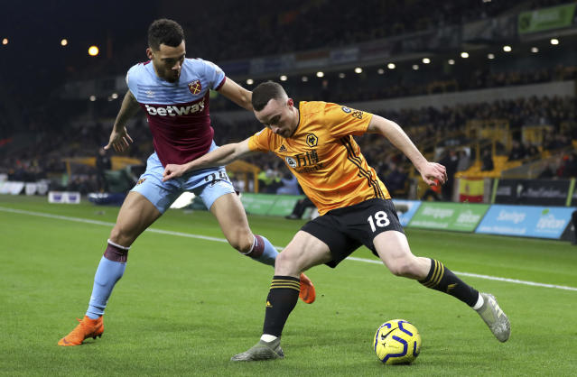 West Ham United's Ryan Fredericks, left, and Wolverhampton Wanderers's Diogo Jota during their English Premier League soccer match at Molineux in Wolverhampton, England, Wednesday Dec. 4, 2019. (David Davies/PA via AP)