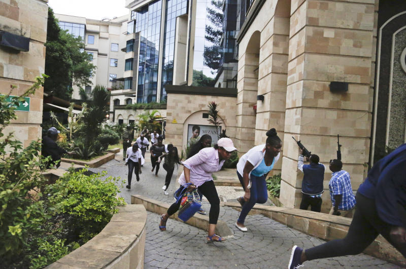 """FILE - In this Tuesday, Jan. 15, 2019 file photo, civilians flee as security forces aim their weapons at a luxury hotel complex attacked by the al-Shabab extremist group, in Nairobi, Kenya. U.N. experts said in a report circulated Tuesday, Nov. 12, 2019 that al-Shabab extremists in Somalia remain """"a potent threat"""" to regional peace and are manufacturing home-made explosives, expanding their revenue sources and infiltrating government institutions. (AP Photo/Khalil Senosi, File)"""