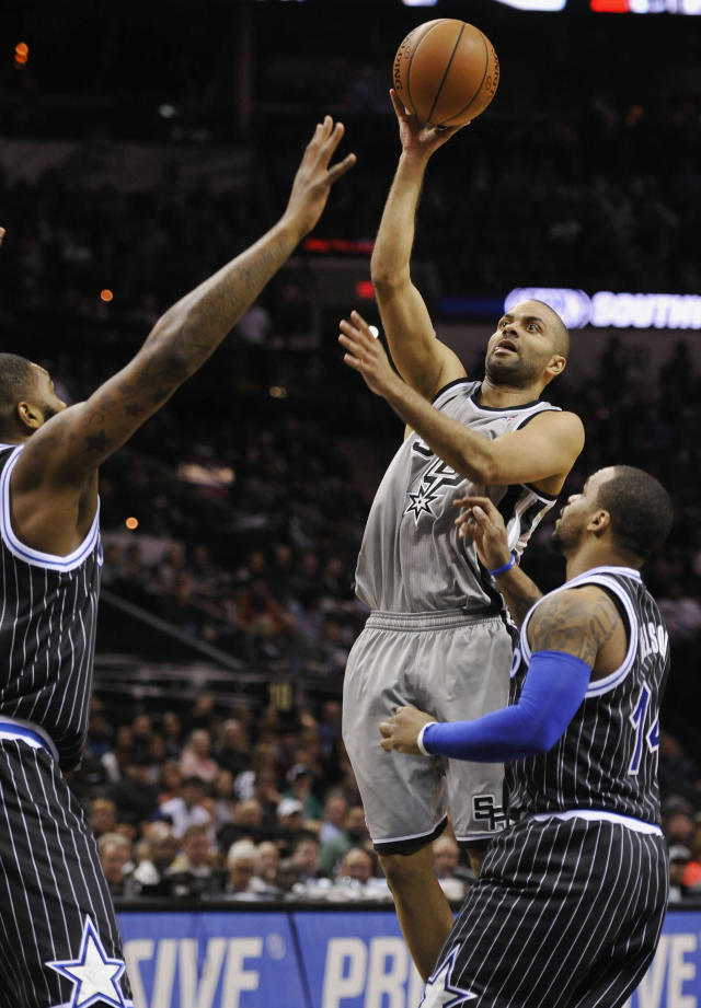 San Antonio Spurs guard Tony Parker, center, of France, shoots against Orlando Magic guard Jameer Nelson, right, and Magic forward Kyle O'Quinn, during the first half on an NBA basketball game on Saturday, March 8, 2014, in San Antonio. (AP Photo/Darren Abate)