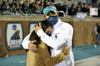 FILE - In this Dec. 5, 2020, file photo, Coastal Carolina coach Jamey Chadwell hugs his wife, Solmaz, after the team's NCAA college football game against BYU in Conway, S.C. Chadwell is The Associated Press college football coach of the year after leading the Chanticleers to a surprising near-perfect season. Chadwell received 16 first-place votes and 88 points from the AP Top 25 panel to finish ahead of Indiana's Tom Allen, who was second with 14 first-place votes and 66 points. (AP Photo/Richard Shiro, File)