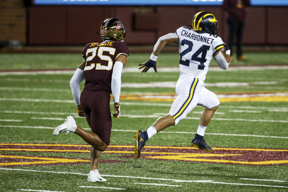Michigan running back Zach Charbonnet (24) breaks away from Minnesota defensive back Benjamin St-Juste (25) for a 70 yard touchdown run in the first quarter of an NCAA college football game Saturday, Oct. 24, 2020, in Minneapolis. (AP Photo/Bruce Kluckhohn)