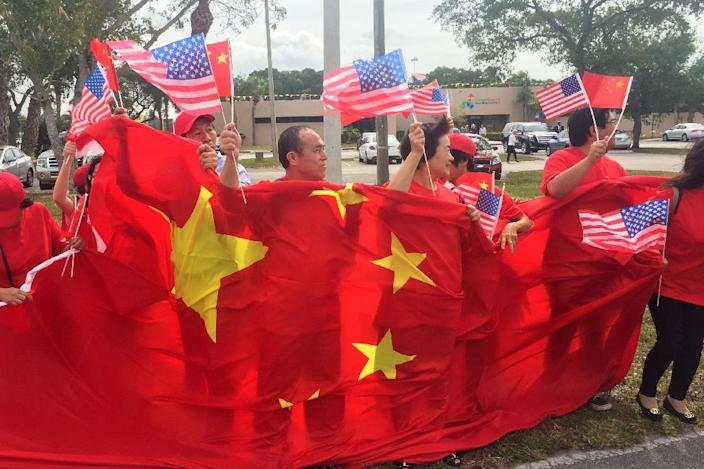 A group of China supporters wave Chinese and US flags as they wait for the arrival of Chinese President Xi Jinping at Palm Beach international airport on April 06 2017 (AFP Photo/Michele Eve SANDBERG)