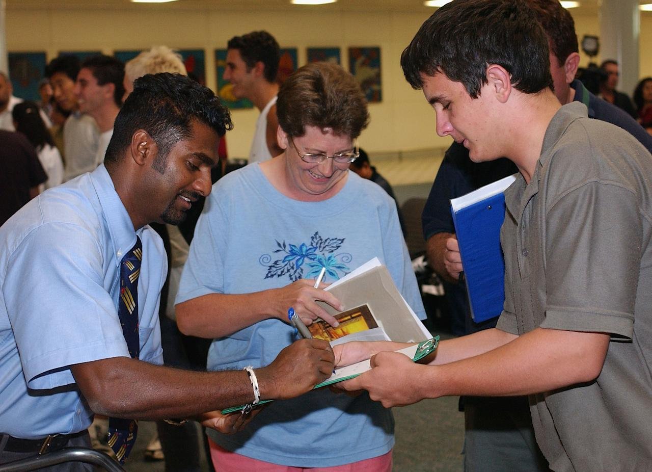BRISBANE - DECEMBER 11:  Muttiah Muralitharan of Sri Lanka signs autographs for fans after the Sri Lankan cricket team arrived at Brisbane International Airport in Brisbane, Australia on December 11, 2002. Sri Lanka are in Australia to play in the VB One-day  Cricket series against England and Australia. (Photo by Darren England/Getty Images)