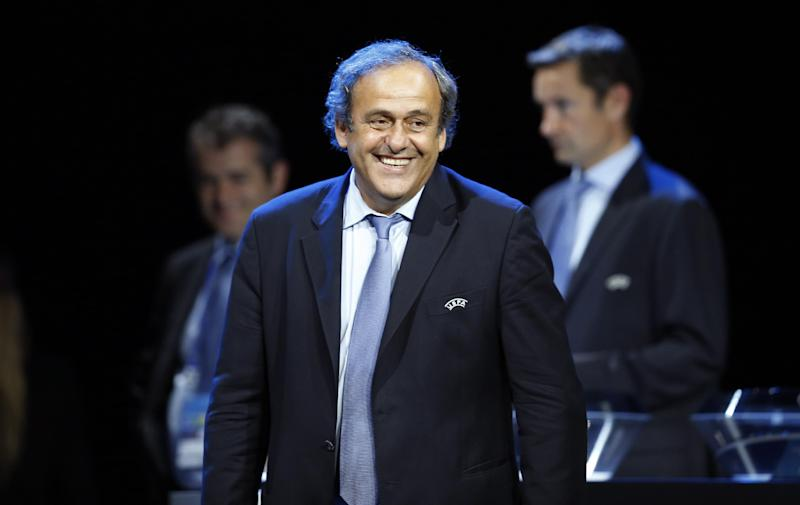 UEFA President Michel Platini smiles as he attends the draw for the 2014/2015 European Champions League group stages, on August 28, 2014 in Monaco (AFP Photo/Valery Hache)