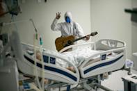 A hospital worker plays guitar for a Covid patient in Brazil, where confusion often reigns as the federal, state and local governments squabble over policy measures to contain the pandemic