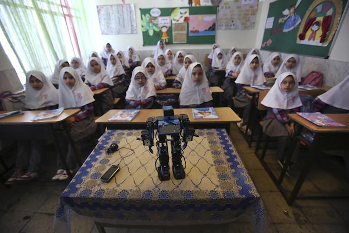 """In this picture taken on Monday, Feb. 24, 2014, Veldan, a humanoid praying robot which is built by Iranian schoolteacher Akbar Rezaie, performs morning prayer in front of Alborz elementary school girls in the city of Varamin some 21 miles (35 kilometers) south of the capital Tehran, Iran. Rezaei who has built a robot to show to children how to execute daily prayers, has innovated an amusing way of encouraging young children to say their daily prayers by using the science of robotics. Out of personal interest and unrelated to his field of study, Akbar Rezaei attended private robotics classes and acquired the skill of assembling and developing customized humanoid robots. He built the robot at home with basic tools and gave it the designation """"Veldan"""", a term mentioned in Quran meaning: """"Youth of Heaven"""". By applying some mechanical modifications such as adding up two extra engines Akbar Rezaei managed to let the robot perform praying movements, such as prostration, more easily.(AP Photo/Vahid Salemi)"""