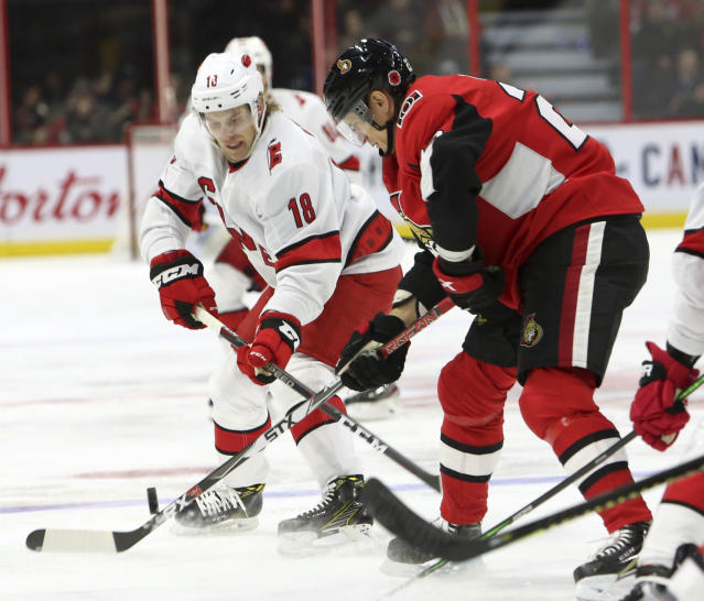 Ottawa Senators Nikita Zaitsev(22) and Carolina Hurricanes Ryan Dzingel (18) try to control a bouncing puck during first period NHL hockey action in Ottawa, Saturday Nov. 9, 2019. (Fred Chartrand/The Canadian Press via AP)