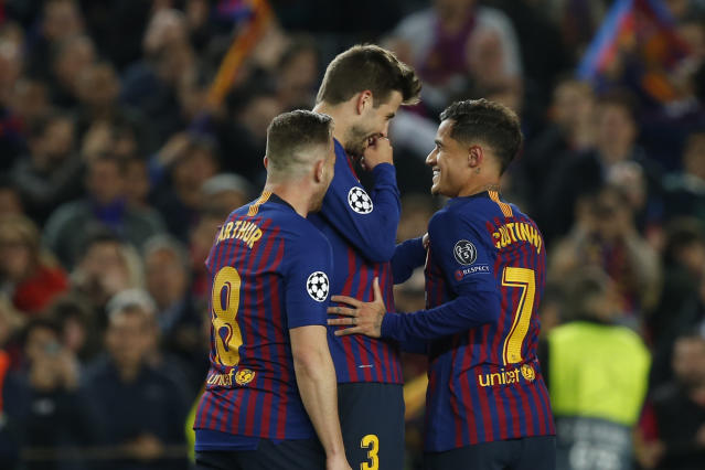 Barcelona forward Philippe Coutinho, right, speaks with Barcelona defender Gerard Pique, center, after scored his side's third goal during the Champions League quarterfinal, second leg, soccer match between FC Barcelona and Manchester United at the Camp Nou stadium in Barcelona, Spain, Tuesday, April 16, 2019. (AP Photo/Joan Monfort)