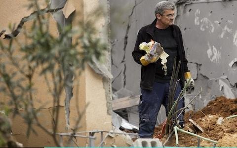Robert Wolf stands inside his house that was hit by a rocket in the village of Mishmeret, north of Tel Aviv - Credit: Amir Levy/Getty Images