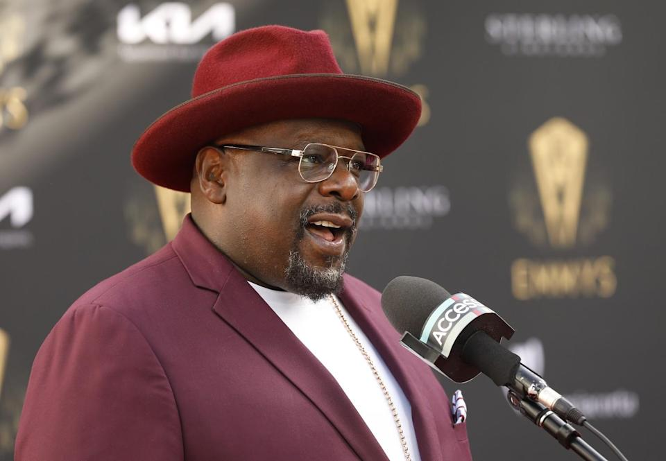 Cedric the Entertainer, wearing a purple suit and hat, speaks into a microphone