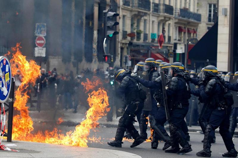 Riot police protect themselves from flames during clashes (REUTERS)