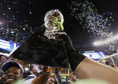 Seattle Seahawk players celebrate with the Vince Lombardi trophy after defeating the Denver Broncos in the NFL Super Bowl XLVIII in East Rutherford