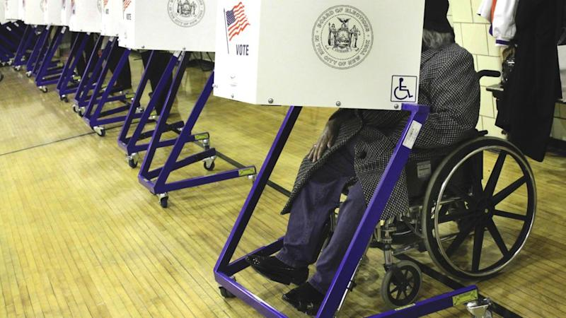 A woman in a wheelchair casts her vote in a school gym in New York's Harlem neighborhood, Tuesday, Nov. 2, 2010. (AP Photo/Richard Drew)