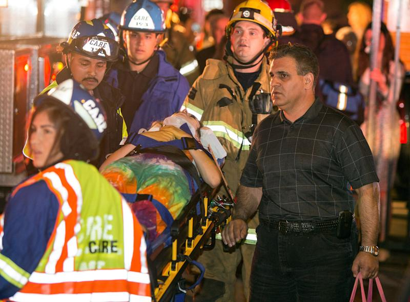 A parent accompanies his injured daughter as firefighters carry her from Servite High School after a stage collapsed during a student event at the high school in Anaheim, Calif., Saturday, March 8, 2014. Authorities said 30-40 people were rushed to hospitals with mainly minor injuries. (AP Photo/Kevin Warn)