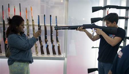 A woman uses a smart phone to photograph a young man holding a shotgun at an exhibit booth at the George R. Brown convention center, the site for the National Rifle Association's (NRA) annual meeting in Houston, Texas