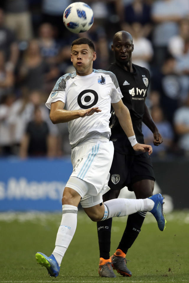 Minnesota United forward Christian Ramirez (21) heads the ball away from Sporting Kansas City defender Ike Opara, back, during the first half of an MLS soccer match in Kansas City, Kan., Sunday, June 3, 2018. (AP Photo/Orlin Wagner)