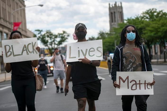 "Protesters march with three placards stating ""BLACK Lives Matter"" in the aftermath of widespread unrest following the death of George Floyd on June 1, 2020 in Philadelphia, Pennsylvania. Demonstrations have erupted all across the country in response Floyd's death in Minneapolis, Minnesota while in police custody a week ago. (Photo by Mark Makela/Getty Images)"