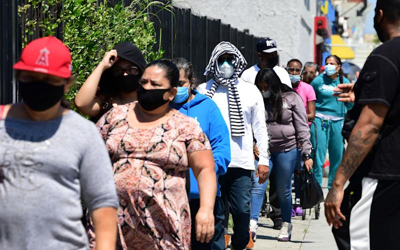 People wear their face masks waiting in line for an emergency food distribution at the 88th Street Temple Church of God in Christ on April 14, 2020 in Los Angeles, California, during the coronavirus pandemic. (Photo by Frederic J. BROWN / AFP) (Photo by FREDERIC J. BROWN/AFP via Getty Images)