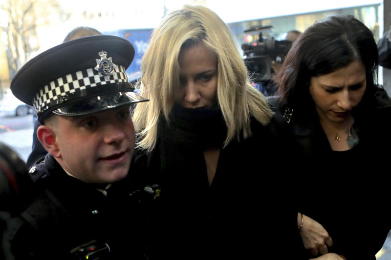 Love Island TV presenter Caroline Flack, centre, escorted by police, as she arrives at Highbury Magistrates' Court in London, Monday, Dec. 23, 2019. Flack has stepped down as host of the upcoming winter series of the TV dating show, Love Island, after being charged with assault of former professional tennis player and model Burton. (AP Photo/Petros Karadjias)