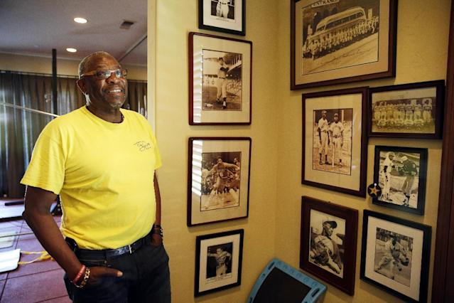 In this March 13, 2014 photo, Dusty Baker looks at walls covered with old photographs of players and teams that impacted him in the gymnasium of his home in Granite Bay, Calif. Out of uniform for the first time since taking 2007 off between managerial jobs with the Cubs and Reds, Baker is not slowing down much from his pressure-packed days in the dugout. (AP Photo/Eric Risberg)