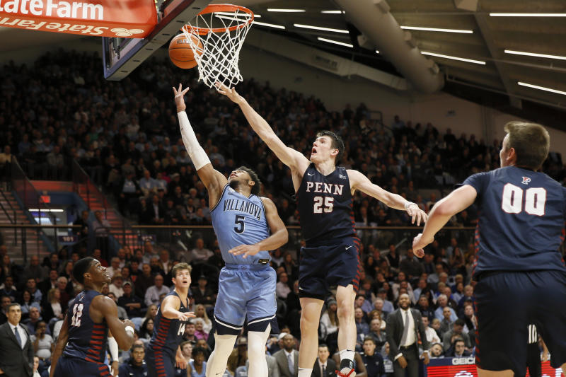 Villanova's Justin Moore (5) goes up for a shot past Pennsylvania's AJ Brodeur (25) during the second half of an NCAA college basketball game Wednesday, Dec. 4, 2019, in Villanova, Pa. (AP Photo/Matt Slocum)