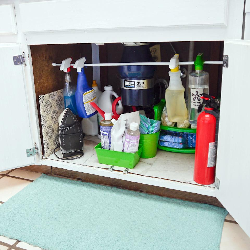 <p>Use a clothing rod to hang your spray bottles to save space. </p>