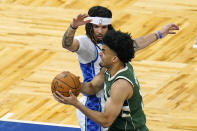 Milwaukee Bucks forward Jordan Nwora, right, goes past Orlando Magic guard Cole Anthony on his way to the basket during the first half of an NBA basketball game, Sunday, April 11, 2021, in Orlando, Fla. (AP Photo/John Raoux)