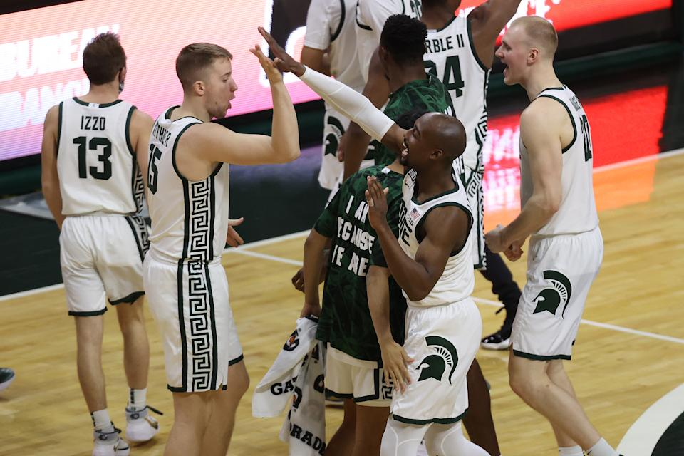 Joshua Langford of the Michigan State Spartans celebrates a 70-64 win over the Michigan Wolverines with teammates at the Breslin Center on March 07, 2021 in East Lansing, Michigan. (Photo by Gregory Shamus/Getty Images)