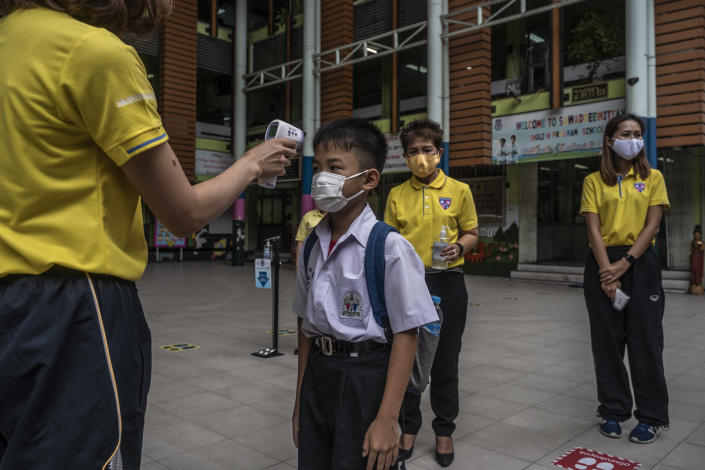 Returning students have their temperature checked on the first day back at Sawasdee Wittaya Primary School in Bangkok, July 1, 2020. (Adam Dean/The New York Times)