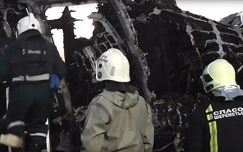 <span>Firefighters work near the burned fuselage at Sheremetyevo airport</span> <span>Credit: Russian investigative committee/TASS/Barcroft </span>