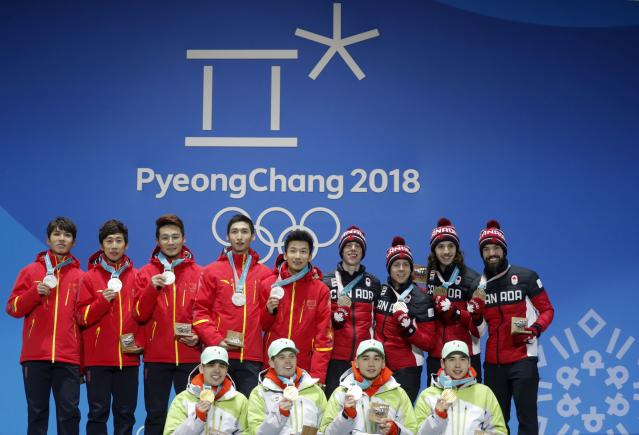 Medals Ceremony - Short Track Speed Skating Events - Pyeongchang 2018 Winter Olympics - Men's 5000m Relay - Medals Plaza - Pyeongchang, South Korea - February 23, 2018 - Gold medalists Viktor Knoch, Csaba Burjan, Liu Shaoang and Sandor Liu Shaolin of Hungary, silver medalists Wu Dajing, Han Tianyu, Xu Hongzhi and Chen Dequan of China and bronze medalists Samuel Girard, Charles Hamelin, Charle Cournoyer and Pascal Dion of Canada on the podium. REUTERS/Eric Gaillard