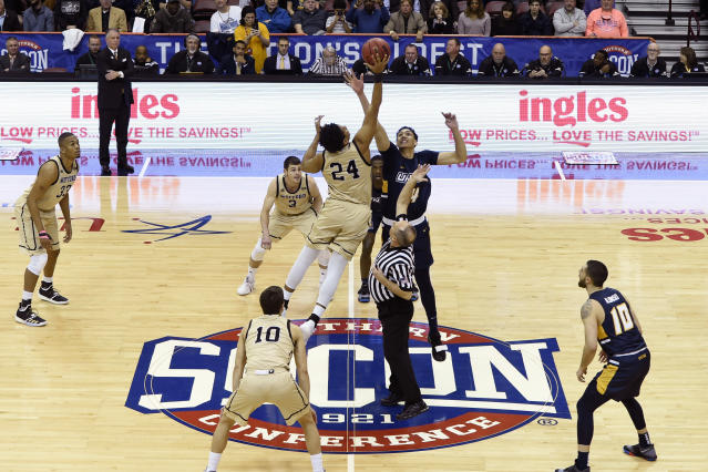 Wofford forward Keve Aluma (24) and UNC-Greensboro forward Kyrin Galloway (14) tip off for the start of an NCAA college basketball game for the Southern Conference tournament championship, Monday, March 11, 2019, in Asheville, N.C. (AP Photo/Kathy Kmonicek)