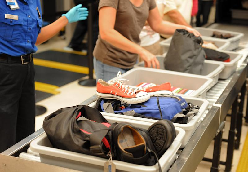 "FILE - In this Aug. 3, 2011, file photo, airline passengers retrieve their scanned belongings while going through the Transportation Security Administration security checkpoint at Hartsfield-Jackson Atlanta International Airport, in Atlanta. Airline executives said Tuesday, Oct. 16, 2012, at a global aviation conference that Airport security needs to undergo a radical overhaul or else passengers will become further disgruntled, lines will grow and terminals will be overwhelmed. ""We simply can't cope with the expected volume of passengers with the way things are today,"" said Tony Tyler, director general and CEO of the International Air Transport Association, the airlines' trade group. (AP Photo/Erik S. Lesser, File)"