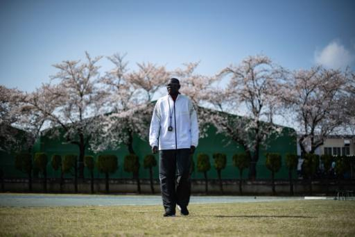 South Sudan coach Joseph Rensio Tobia Omirok supervises his athletes to a backdrop of cherry blossom as they train in Maebashi, north of Tokyo, where they were stranded after the Games were postponed