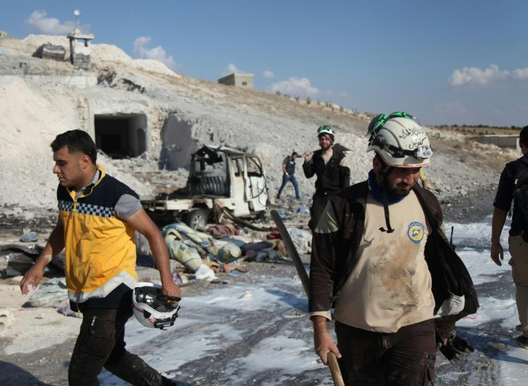 Syrian civil defence members on search through wreckage on September 8, 2018 left by an air strike on Idlib's southern town of Hass