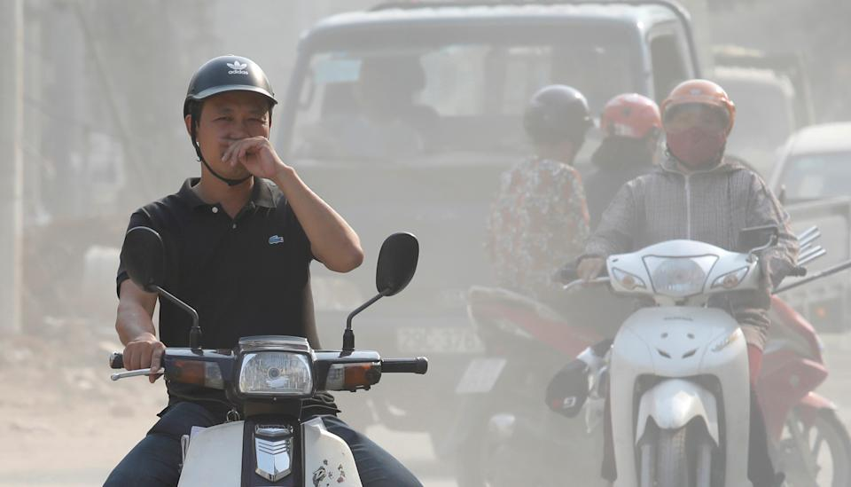 A man covers his nose as he drives through an air polluted street in Hanoi, Vietnam October 1, 2019. REUTERS/Kham