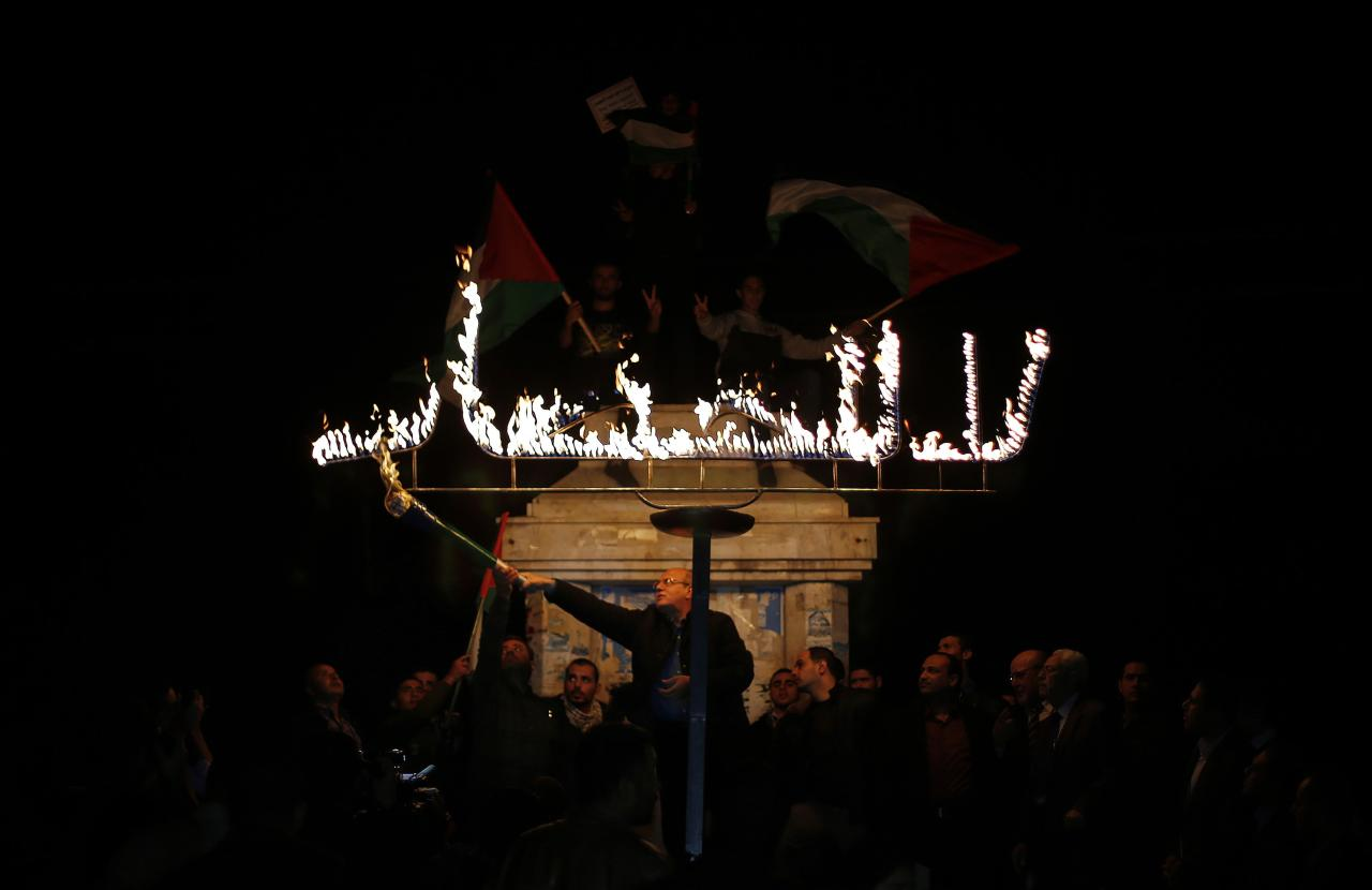 """A Palestinian uses a torch to light a sign that reads """"no to the blockade"""" during a protest against the blockade on Gaza in Gaza City November 30, 2013. Israel imposed a blockade on Gaza in 2007 after Islamist group Hamas seized control of the territory in a brief civil war with Western-backed Palestinian President Mahmoud Abbas's Fatah party. REUTERS/Suhaib Salem (GAZA - Tags: CIVIL UNREST POLITICS)"""