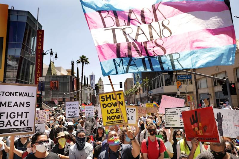 """HOLLYWOOD-CA-JUNE 14, 2020: Raymond Quitugua, of Sacramento, center, waves a flag that reads """"Black Trans Lives Matter"""" as people fill the street on Hollywood Boulevard during a solidarity march with Refuse Fascism and All Black Lives Matter in Hollywood, California on Sunday, June 14, 2020. (Christina House / Los Angeles Times)"""
