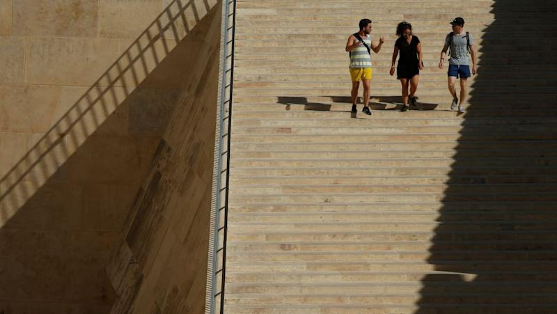 People walk down the staircase at the entrance to Valletta towards the bus terminus, outside the city walls of Valletta