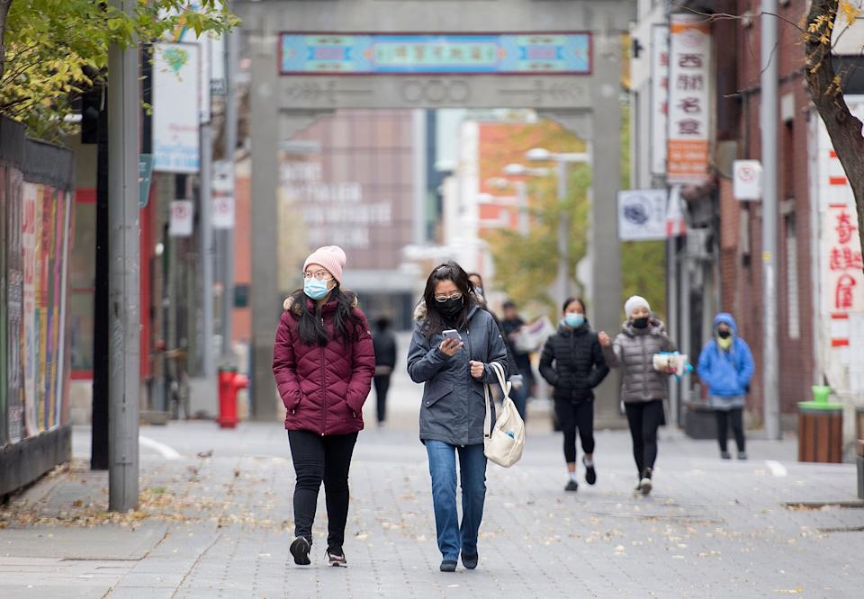People make their way along a street in Montreal's Chinatown. (Photo: Graham Hughes / The Canadian Press)