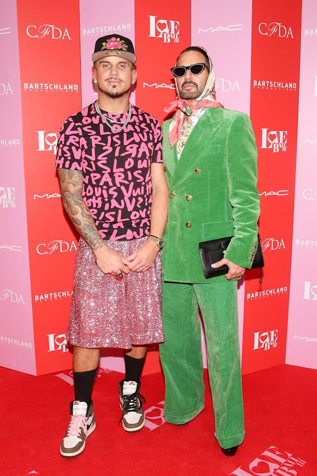 <p>The fashion designer showed up in a bright green suit and multicolored heard scarf. His husband Char rocked a pink and black Louis Vuitton T-shirt, pink sequined basketball shorts and Nike sneakers.</p>