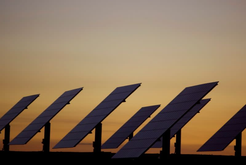 FILE PHOTO: The sun sets beyond solar panels at a power plant in Amareleja