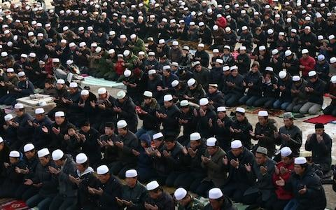 Muslims pray outside a mosque during Eid al-Adha celebrations in Wuzhong - Credit: Corbis News/ Jie Zhao
