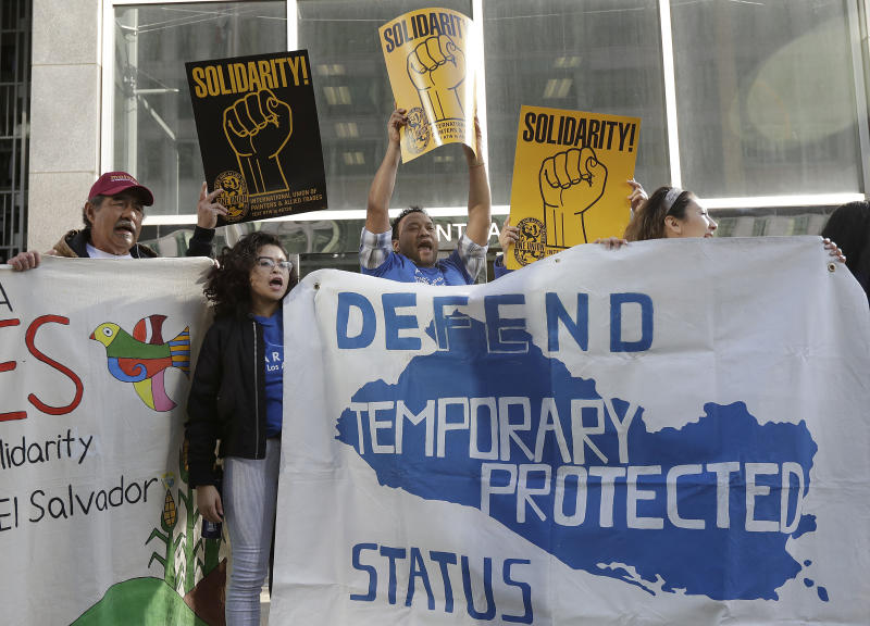 """FILE - In this Monday, March 12, 2018, file photo, supporters of temporary protected status immigrants hold signs and cheer at a rally before a news conference announcing a lawsuit against the Trump administration over its decision to end a program that lets immigrants live and work legally in the United States outside of a federal courthouse in San Francisco. A judge on Wednesday, Oct. 3, 2018, blocked the Trump administration from ending protections that let immigrants from four countries live and work legally in the United States, saying the move would cause """"irreparable harm and great hardship."""" (AP Photo/Jeff Chiu, File)"""