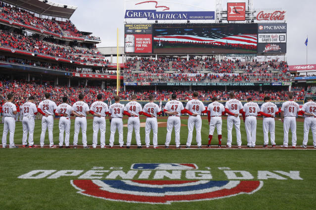 The Cincinnati Reds stand for the national anthem before an opening day baseball game against the Washington Nationals, Friday, March 30, 2018, in Cincinnati. (AP Photo/Gary Landers)
