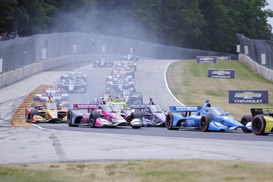 Alex Palou leads a group in a turn during an IndyCar race at Road America in Elkhart Lake, Wisc., Sunday, June 20, 2021. (AP Photo/Jeffrey Phelps)