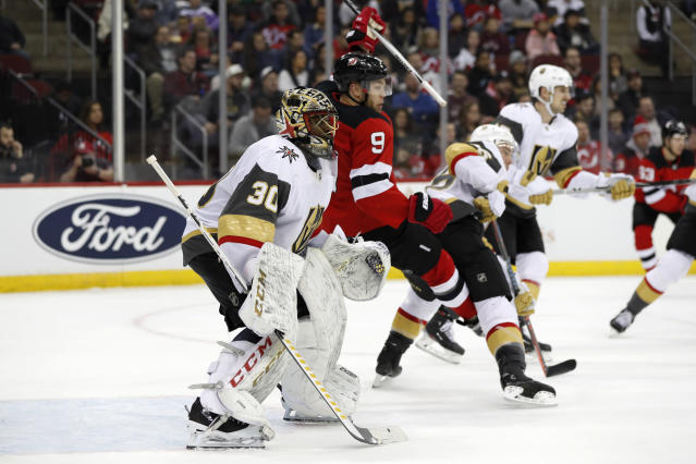 New Jersey Devils left wing Taylor Hall (9) trips in front of Vegas Golden Knights goaltender Malcolm Subban (30) during the second period of an NHL hockey game, Tuesday, Dec. 3, 2019, in Newark, N.J. (AP Photo/Kathy Willens)