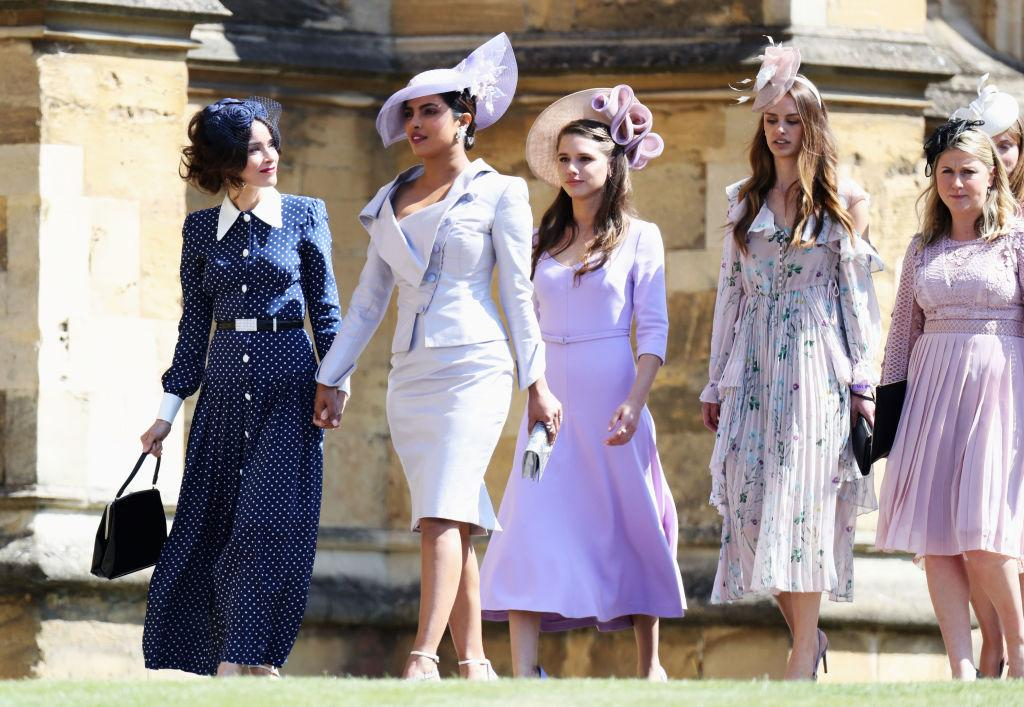 <p>Meghan's Suits co-stars, Abigail Spencer and Priyanka Chopra arrive at St. George's chapel. Abigail wears a navy blue polka dot dress and Chopra wears Vivienne Westwood and a Philip Treacy hat. [Photo: Getty] </p>