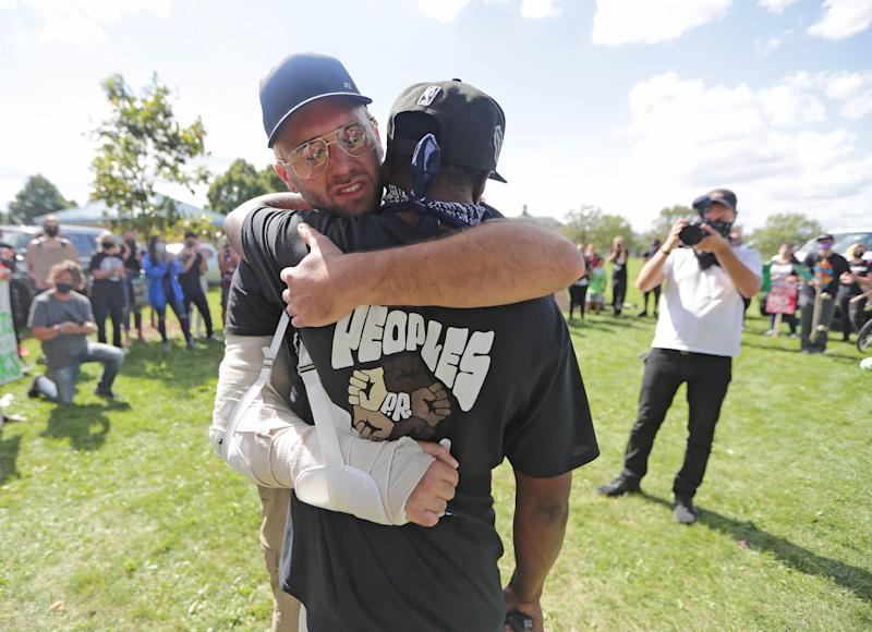 Community organizer Khalil Coleman, right, gets a hug from Gaige Grosskreutz, 26, who was shot in the arm in Kenosha, before a march through the streets of Milwaukee on Sept. 5.