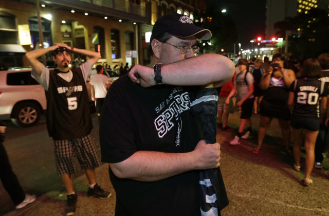 San Antonio Spurs fans Todd Beach, right, and Steven Thompson, left, stand outside a restaurant with other fans as they watch the Spurs fall to the Miami Heat in Game 7 of the NBA Finals basketball championship, Thursday, June 20, 2013, in San Antonio. Miami won the series. (AP Photo/Eric Gay)